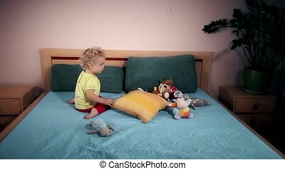 mischievous child throwing toys on bed in bedroom.
