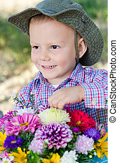 Mischievous little boy with flowers