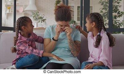 Mischievous mother joking with little girls on sofa - ...