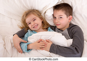Mischievous young brother and sister in bed