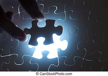 Missing Piece - A hand fitting the last piece of puzzle in...