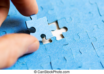 mission complete concept - hand placing last piece of jigsaw puzzle