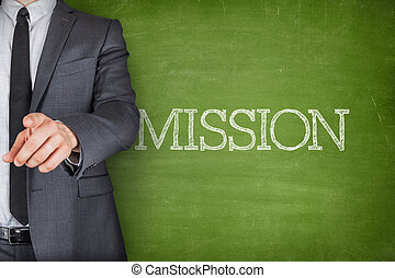 Mission on blackboard with businessman finger pointing