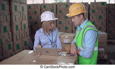 Dolly in of supervisor giving verbal reprimand to the laborer in warehouse