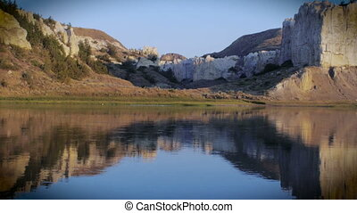 Locked down shot of the Missouri River at sunrise with the reflection of limestone cliffs and sky on the still water.