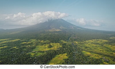 Mist at volcano eruption aerial. Clouds of haze over Mayon mount peak. Tropical farmland at lush green valley with plants and grasses. Nobody nature landscape of Philippines countryside with mountain
