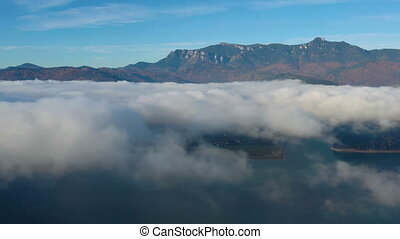 Mist cloud over mountain lake, flying drone in Romanian ...