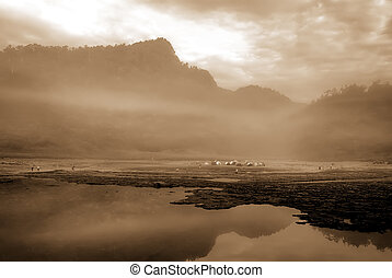 It is a lake with mist and mountain.
