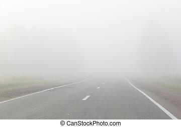 mist over asphalt road at dawn