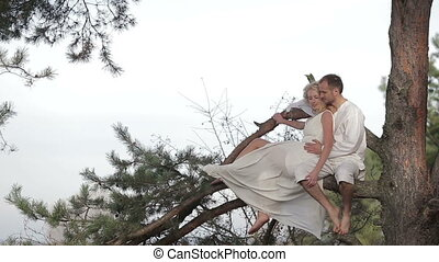 Misterious and beautiful young couple lying together on a tree banch in the woods