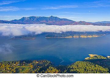 Misty cloud over lake at sunrise