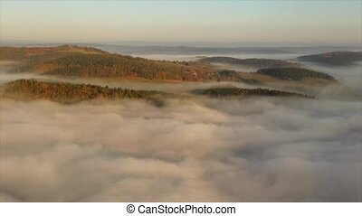 Misty clouds over the autumn forests, aerial. - Misty clouds...