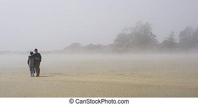 misty couple - a couple walking on a misty beach in the...