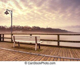 Misty dusk on the landmark fishing pier, pier railings. Wooden mole