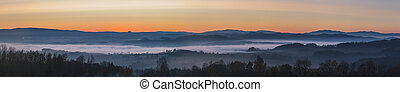 misty landscape at sunset, mountains rising from clouds of fog, clear sky