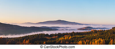 misty landscape at sunset, mountains rising from clouds of fog, clear sky - mountain Klet, Czech republic