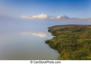 Misty landscape with a lake and mountains.