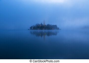 Misty morning in lake Bled and famous island with old...