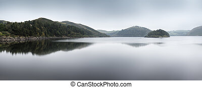 Misty morning landscape panorama over calm lake in Autumn