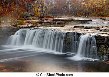 Morning mist rises over Indiana's Lower Cataract Falls surrounded by a vibrant autumn landscape.