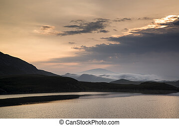 Misty mountain landscape at sunrise reflected in lake