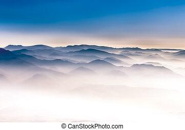 Misty mountains landscape view with blue sky - Misty ...