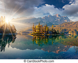 Misty summer morning on the Eibsee lake in German Alps.