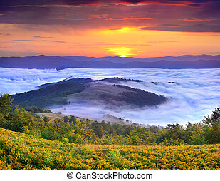misty sunrise in the mountains at the summer