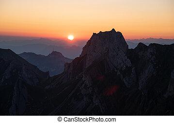 Misty sunset with beautiful silhouette of mountain range in Switzerland