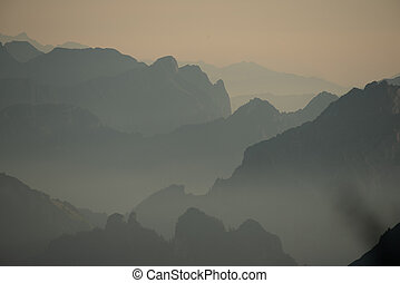 Misty sunset with beautiful silhouette of mountain range in Switzerland