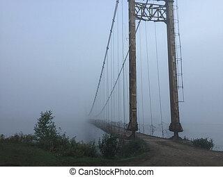 Misty suspension bridge fog view. Altai village bridge. Early misty morning