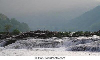 Misty Waterfall Loop - Water cascades over rock ledges with...