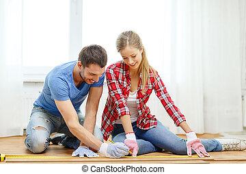 misurazione, sorridente, legno, coppia, pavimentazione