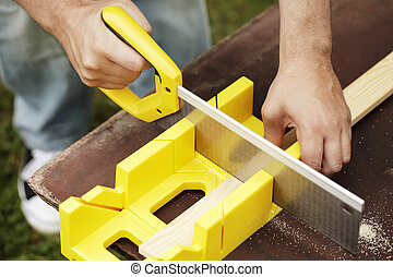 Miter Box - Man cutting a slat of wood using a saw and miter...