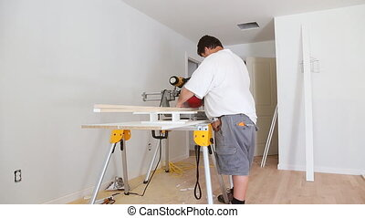 Miter Saw on a construction site with a worker in contractor...