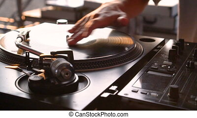Mix and scratch, hands of a DJ on vinyl and mixer knobs. ...