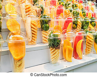 Mix fruits in a plastic glass on wooden shelves