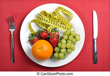 mix fruits on a plate with measure tape in diet concept on red mat