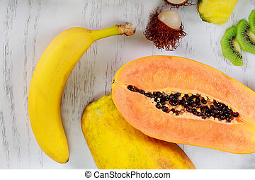 Mix of colored fruits on white wooden background composition of tropical fruits healthy eating and food background