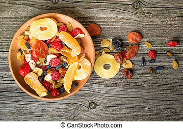 Mix of dried and candied fruit in bowl on a wooden background, top view