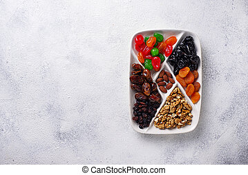 Mix of dried fruits and nuts in plate. Top view