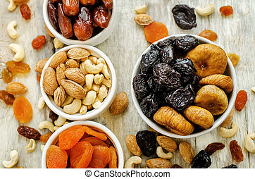 mix of dried fruits and nuts on a white wood background....