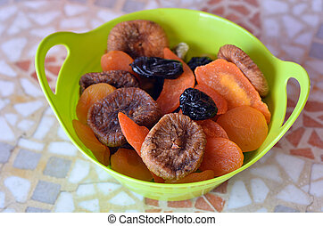 Mix of dried fruits in a green bowl during the Jewish holiday Tu Bishvat