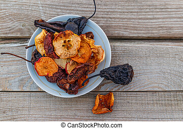 Mix of dried fruits in a plate on wooden table. Top view