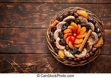 Mix of dried fruits in a small wicker basket on wooden...