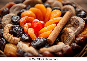 Mix of dried fruits in a small wicker basket on wooden table...