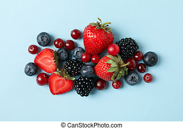 Mix of fresh berries on blue background, top view