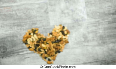 Mix of healthy raw nuts in heart shape on wooden background....