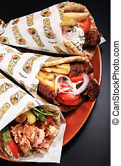 chicken lamb and pork rolled on a pita bread isolated on a black background