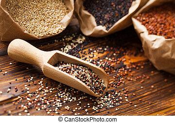 Mix of quinoa seeds in the wooden scoop